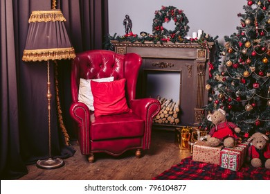 Red armchair in modern style in the New Year's retro interior with a Christmas tree, a fireplace and gift packages
