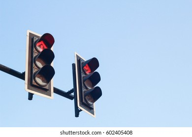 Red arrow color on the traffic light with blue sky in background