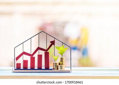 Gráfico de flecha roja y moneda apilada con el valor de la planta arriba puesto en el modelo de casa en el parque público, Ahorro para comprar casa o préstamo para el concepto de inversión de inversión inmobiliaria.