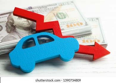Red arrow graphics down on the background of the car and a stack of money cash dollars. Concept of falling car market, insurance, lower prices, repair costs