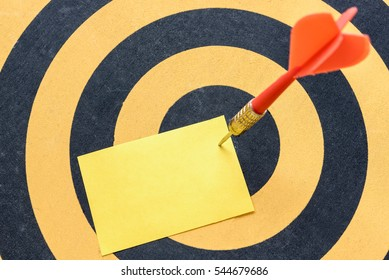 Red arrow hitting yellow blank note over in bullseye on dartboard background, Business opportunities success concept
