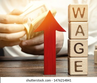 Red arrow up near wooden blocks with the word Wage and a businessman. Salary increase concept. Wages rate. Revenue growth and profits. Successful business. Career rise. Promote. Stability