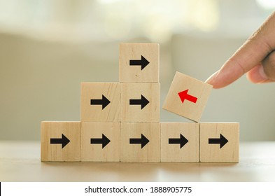 The red arrow, the wood block, the business man's hand is pointing in, in contrast to the black arrow on the wooden table. Think of independent business ideas that are different and unique.