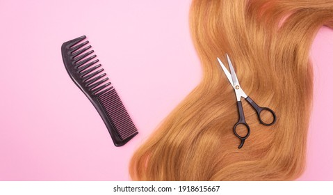 Red artificial hair on a pink background, comb and scissors. The concept of hairstyle, haircut, hair care.
