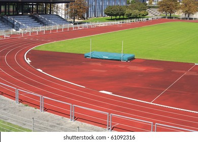 Red athletics track with green field