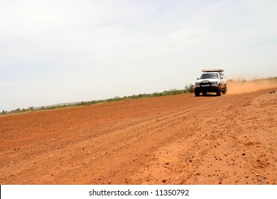 Red Australian rural road with approaching white off road car.Tanami road, Western Australia