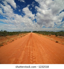 Red Australian Rural Road with Cloudy Blue Skies