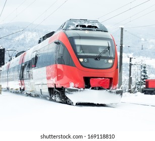 Red austrian train on snowy tracks