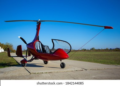Red autogyro parked at the airfield in sunny day. Gyrocopter against the blue sky.