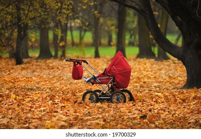 Red baby carriage on autumn colors park background. Focus on carriage.