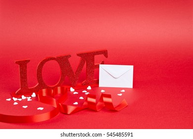 Red background with big glitter love sign with ribbon curled into heart and white confetti and message