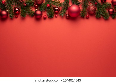 Red background with Christmas balls and fir branches. Merry Christmas or New Year decoration with copy space