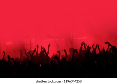 Red background with a crowd of cheering people at a concert. People with their hands up