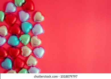 Red background with multicolored heart rests in the concept of Valentine's Day. Candy hearts on a red background in vintage style. Copy space on red background and heart.