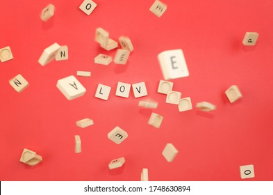 red background with scrabble pieces with the word love and pieces falling