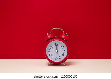 red background wall with red alarm clock isolated on white table. front angle view. 12 four o'clock. close up shot.
