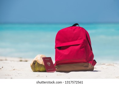 Red backpack, coconut and foreign russian passport on white sand with azure ocean water on the background