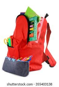 Red backpack with colourful stationary and pencil case isolated on white background