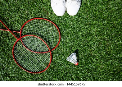 Red badminton rackets and shuttlecock lie on the artificial grass of a sports stadium, white sneakers stand next to them. Amateur badminton set. Concept of summer hobby, outdoor sports, entertainment.