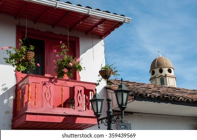 Red balcony and the tower of a church in background under blue sky