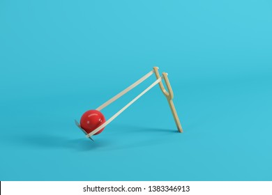 Red ball in a slingshot on blue background. Minimal fruit idea concept.