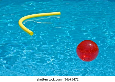 red ball and yellow foam noodle in the blue water of the pool