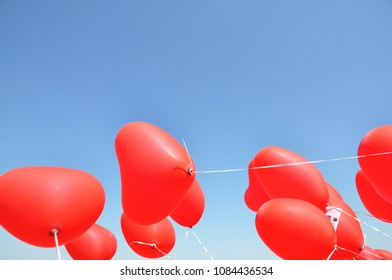 Red ballons with the messages in the blue sky