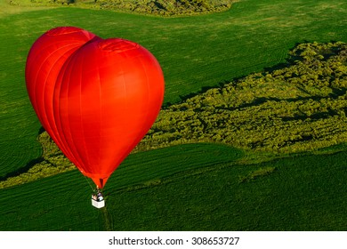 Red balloon in the form of heart over green fields and forests