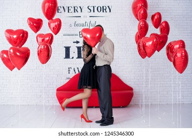 Red balloon heart covering couple kiss. Red heart-shaped balloons. Set of Air Balloons. Love. Holiday celebration. Valentine's Day party decoration. Metallic red colour Heart air ballons on white bric
