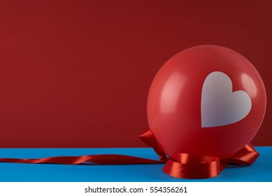 Red balloon with heart and ribbon against red background. Love card concept with copy space. Valentine's day theme