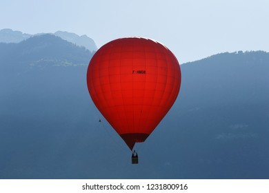 Red balloon on an early morning flight over Lake Annecy France