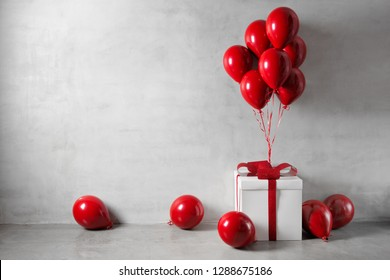 Red balloons and white gift box on concrete wall background