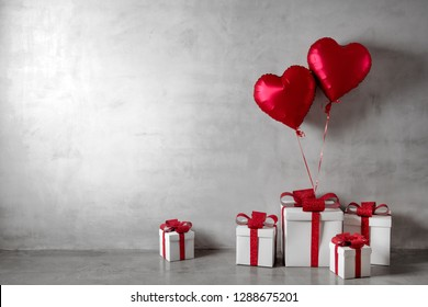 Red balloons and white gift boxes on concrete wall background