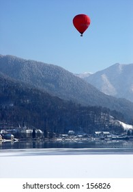 Red baloon over snow covered mountains
