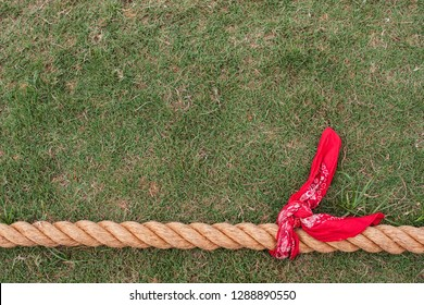 Red bandana is attached to thick rope for tug of war contest