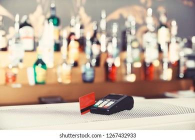 Red bankcard inserted in reader on defocused background. Electronic finance and shopping concept. Payment for drink in bar. EDC machine or credit card terminal for cashless payments.