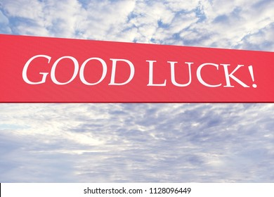"""Red banner with the inscription """"Good luck!"""" against the sky with clouds"""