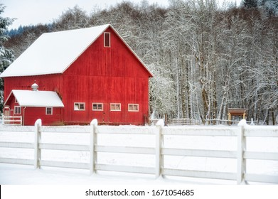 A red barn and barnyard surrounded with a white fence stand out in this winter landscape.