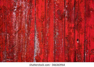 Red barn board wall from farm barn.  Textured and peeling red paint covering the wall.