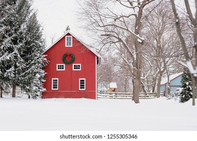 Red barn with Christmas wreath on snowy midwestern day
