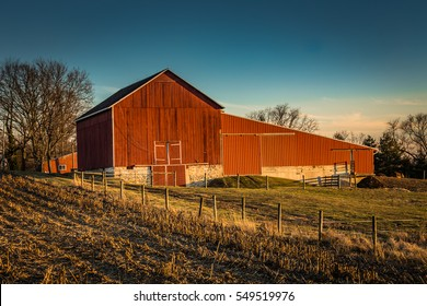A red barn late in the day in the winter with a nearby field and fences.