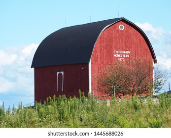 Red barn on hill with blue sky
