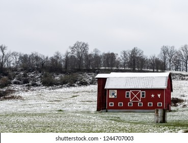 Red barn on a snow-covered hillside in Appalachia on an overcast day.
