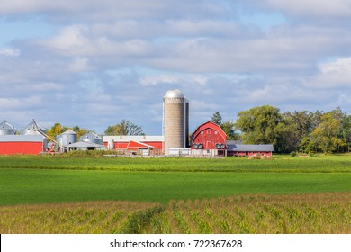 Red barn, outbuildings, silo and corn field panorama in the American Midwest.