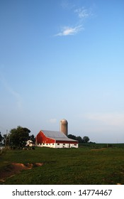 Red barn, a silo, and cows