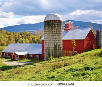 Red barn and silo with a sloping hill and green grass in foreground, trees with fall colors and Vermont mountains in the background under a blue and cloudy sky on a nice autumn day.