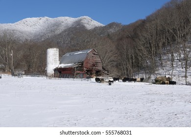 red barn in snow mountains