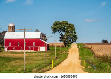 Red barn with white roof by narrow gravel road with low spot marked by two yellow posts in farm country on a sunny day in October, northern Illinois, USA, for rural and agricultural themes