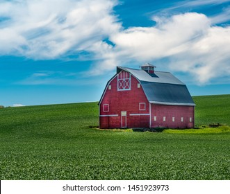 Red barn with white trim on a day with blue sky and clouds