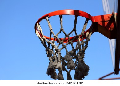 Red basketball basket on a background of blue sky. Cropped shot, horizontal, close-up. Sport and hobby concept.